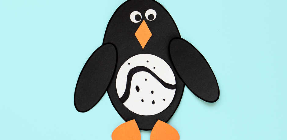 Cute penguin craft made of felt against blue background