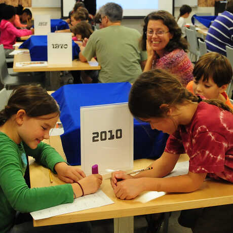 students write on worksheets in a museum classroom
