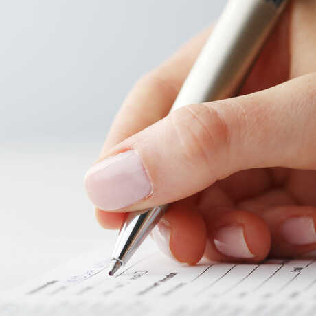 A hand is shown filling out a form