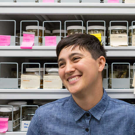 Arachnologist Lauren Esposito in front of a wall of preserved insect specimens