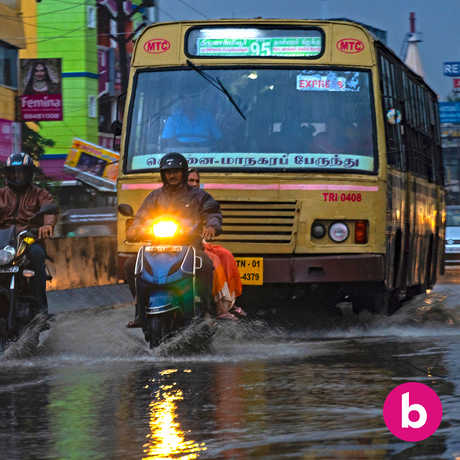 A rainy Chennai street with bus and mopeds