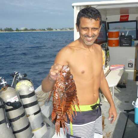 Luiz Rocha holds a caught invasive lionfish