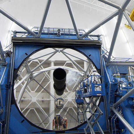 Technicians cleaning the 4-meter mirror inside Chilean telescope