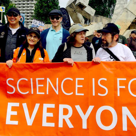 "March for Science banner says ""Science is for Everyone"" held by Academy staff"
