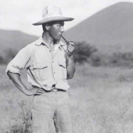 Toshio Asaeda stands in grasslands surrounded by mountains smoking a pipe
