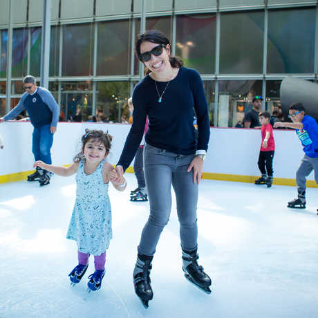 A mother and daughter are all smiles on the ice rink