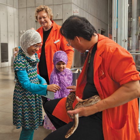 Academy docent introduces two delighted young guests to a python