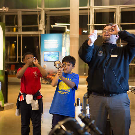 Academy staff demonstrates proper magnifying glass technique to youngsters
