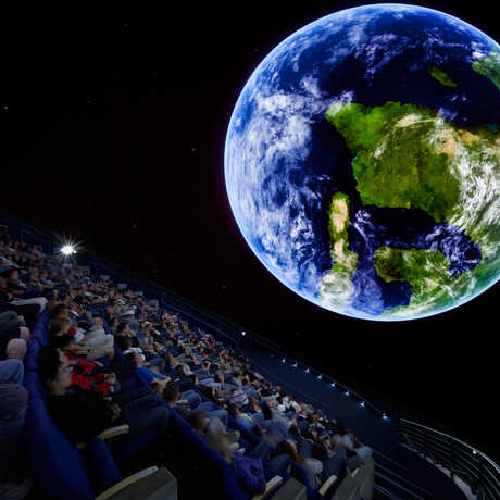 A shot from inside the planetarium of an audience looking at a giant planet Earth