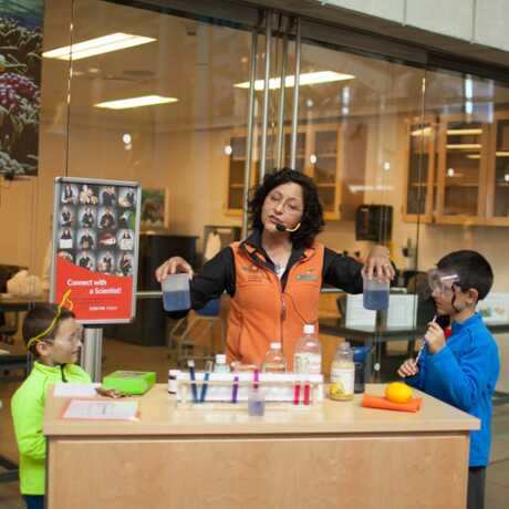 Science demonstration with a docent and young boys in safety goggles