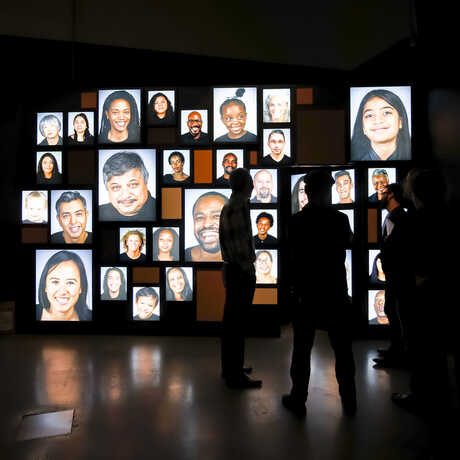 A digital photo mosaic of faces with silhouetted people in front
