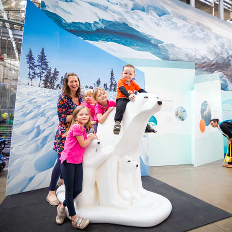 Smiling family poses next to and atop a life-size model of a polar bear