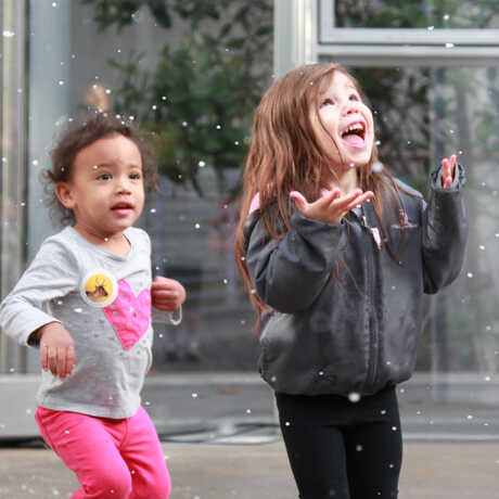 2 young girls delight in snow flurries at the Academy