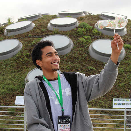 Science Action Club student uses an anemometer on Academy Living Roof