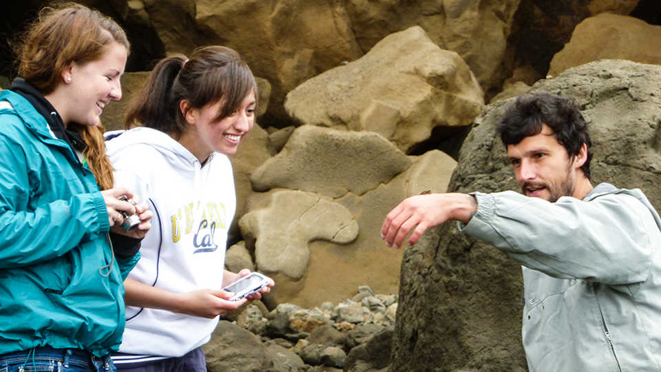 A teacher showing two students a marine organism