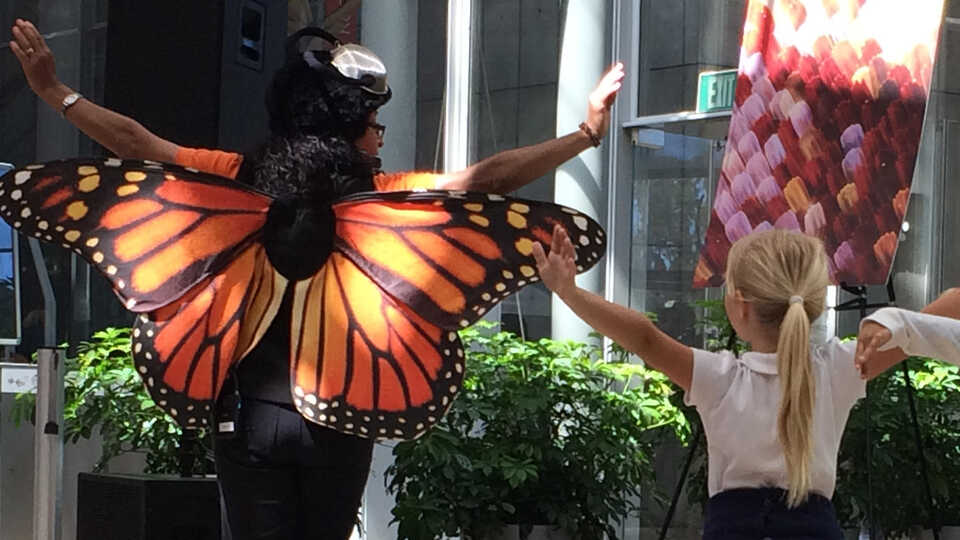 "Presenter dressed as a butterfly ""flying"" with young children"