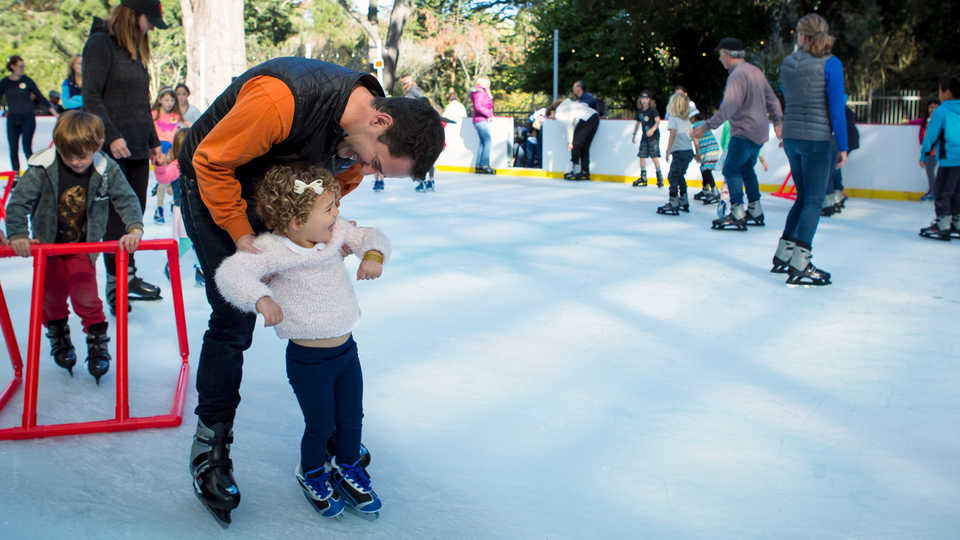 Dad teaches smiling toddler to ice skate at the Academy ice rink